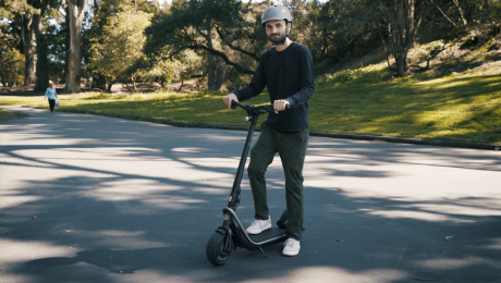 a man on a boosted rev electric scooter with a helmet on because safety